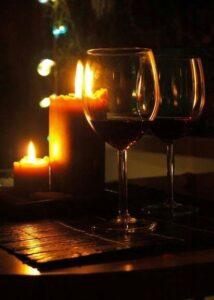 Kaks veinipokaali küünalde taustal